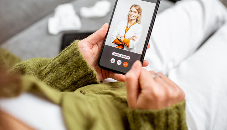 Woman using her phone to video conference with a doctor
