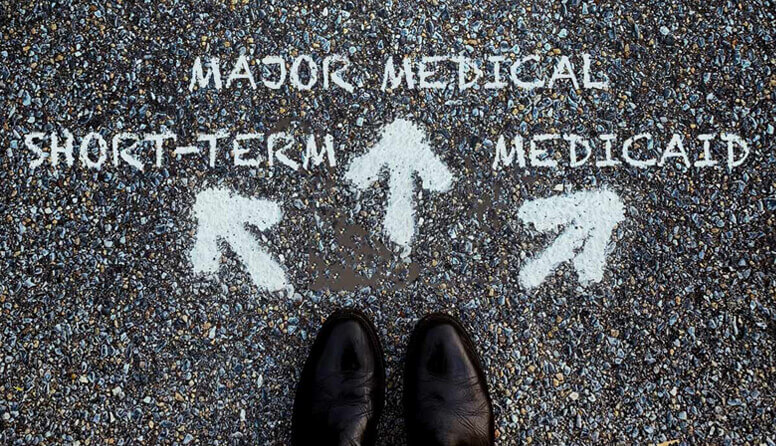 3 arrows painted on asphalt pointing to short-term, major medical, or Medicaid options