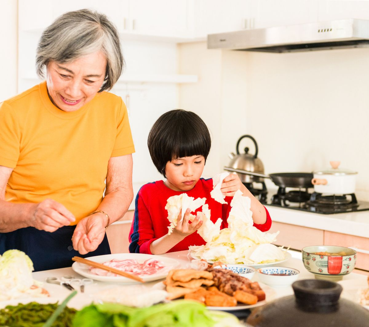 Grandmother and grandson making dinner because the grandmother may have saved with Medicare Savings Program